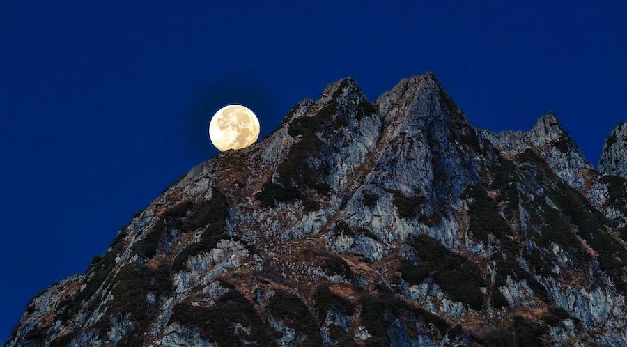 moon behind mountains at night