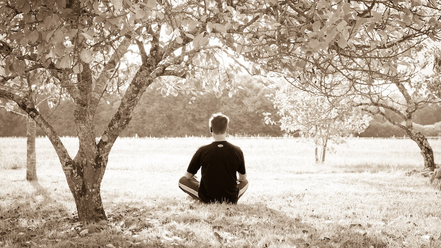 man meditating in a park during the day